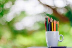 Kulöra blyertspennor i ett exponeringsglas på Bokeh bakgrund arkivfoton