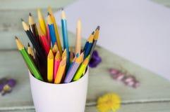 Kulöra blyertspennor i ett exponeringsglas på en träbakgrund royaltyfri fotografi