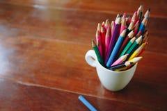Kulöra blyertspennor i ett exponeringsglas på träbakgrund arkivfoto