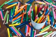 Kulöra blyertspennor i ett exponeringsglas på träbakgrund royaltyfri fotografi