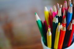 Kulöra blyertspennor i ett exponeringsglas på träbakgrund royaltyfri foto