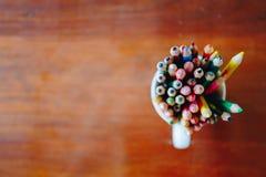 Kulöra blyertspennor i ett exponeringsglas på träbakgrund royaltyfri bild