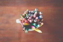 Kulöra blyertspennor i ett exponeringsglas på träbakgrund arkivfoton