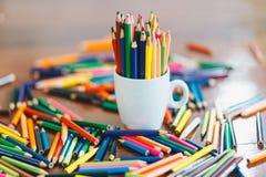 Kulöra blyertspennor i ett exponeringsglas på träbakgrund fotografering för bildbyråer