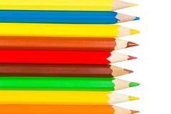 Kulöra blyertspennor i rad på det vänstert arkivfoto