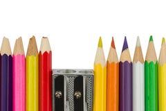 Kulöra blyertspennor med en vässare i packen står i ett r arkivbild