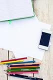 Kulöra blyertspennor, mobiltelefon och papper Fotografering för Bildbyråer