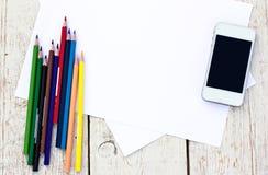Kulöra blyertspennor, mobiltelefon och papper Arkivfoto