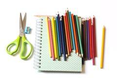 Kulöra blyertspennor och anteckningsbok Fotografering för Bildbyråer