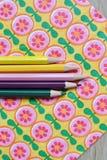 Kulöra blyertspennor och blom- bakgrund Royaltyfri Foto