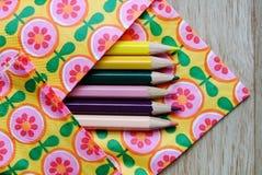 Kulöra blyertspennor och blom- bakgrund Arkivfoton