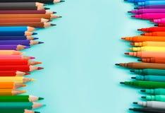 Kulöra blyertspennor och colred markörer på pastellfärgad bakgrund arkivbilder