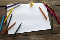 Kulöra blyertspennor och ett ark av papper Royaltyfri Bild
