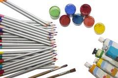 Kulöra blyertspennor och målarfärg Arkivbild