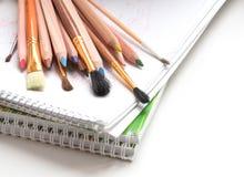 Kulöra blyertspennor och målarfärgborstar Royaltyfri Bild