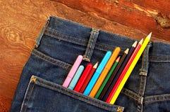 Kulöra blyertspennor och tuschpennor i jeans för en bakficka Royaltyfri Fotografi