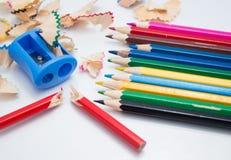 Kulöra blyertspennor och vässarebakgrund royaltyfri bild