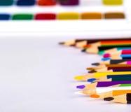 Kulöra blyertspennor och vattenfärger på en vit bakgrund fotografering för bildbyråer