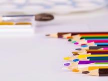 Kulöra blyertspennor och vattenfärger på en vit bakgrund royaltyfri fotografi
