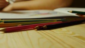 Kulöra blyertspennor på bakgrunden av kvinnliga händer drar den vuxna färgläggningboken lager videofilmer