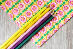 Kulöra blyertspennor på blom- bakgrund Royaltyfri Foto