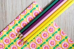 Kulöra blyertspennor på blom- bakgrund Royaltyfria Bilder