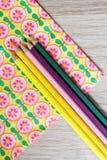Kulöra blyertspennor på blom- bakgrund Arkivfoto