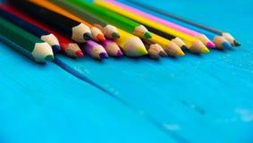 Kulöra blyertspennor på en blå träbakgrund Fotografering för Bildbyråer
