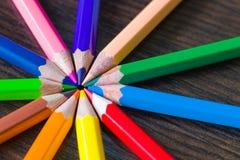 Kulöra blyertspennor på en brun bakgrund Royaltyfri Bild