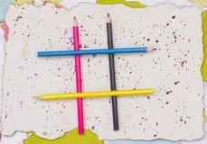 Kulöra blyertspennor på en sönderriven pappersfyrkant Arkivbild