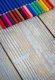 Kulöra blyertspennor på en träbakgrund Royaltyfri Fotografi