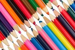Kulöra blyertspennor på ett diagonalt och att trycka på i mitt på en vit stock illustrationer