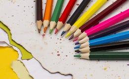 Kulöra blyertspennor på ett sönderrivet papper med gouache färgar lock Arkivbilder
