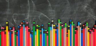 Kulöra blyertspennor på ett svart bräde stock illustrationer