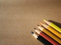 5 kulöra blyertspennor på Kraft papper arkivfoton