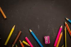 Kulöra blyertspennor, på mörk bakgrund, kan använda som baner eller glida Arkivfoto