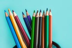 Kulöra blyertspennor på pastellfärgad bakgrund arkivbild