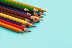 Kulöra blyertspennor på pastellfärgad bakgrund royaltyfria foton