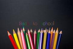 Kulöra blyertspennor på svart tavlabakgrund Arkivfoton