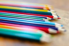 Kulöra blyertspennor på träskrivbordet royaltyfria foton