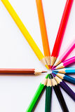 Kulöra blyertspennor på vit bakgrund, i en cirkel arkivbilder