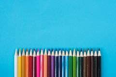 Kulöra blyertspennor som isoleras på blå bakgrund Royaltyfria Bilder
