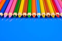 Kulöra blyertspennor som isoleras på blå bakgrund med reflexion Royaltyfria Foton