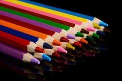 Kulöra blyertspennor som isoleras på svart bakgrund med reflexion Arkivfoto