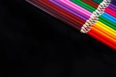 Kulöra blyertspennor som isoleras på svart bakgrund som ligger i motsatta hörn Royaltyfri Fotografi