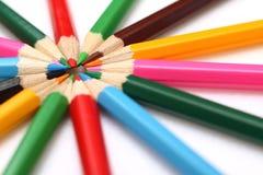 Kulöra blyertspennor som staplas i form av solen Arkivfoto