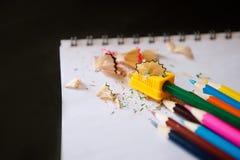 Kulöra blyertspennor, vässare och shavings Arkivfoto