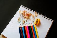 Kulöra blyertspennor, vässare och shavings Royaltyfri Foto