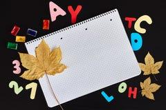 Kulöra bokstäver, målarfärger, höstsidor och tomt ark av anteckningsboken på den svarta bakgrunden fotografering för bildbyråer