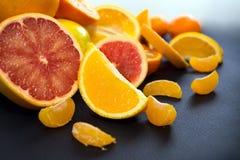 Kulöra citrusfrukter på ett mörker - blå bakgrund Skivor av citruns och peelen Citrus reticulata Citrust paradisi Citrus Limon Arkivbilder